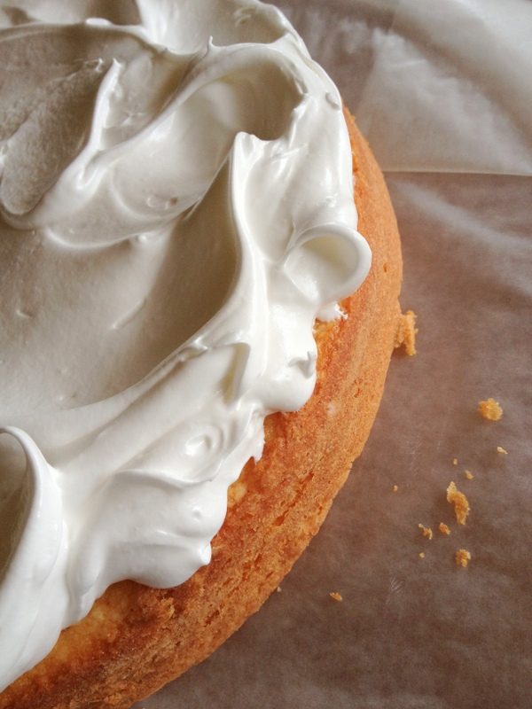The cake layers are baked, and the first swirls of White Mountain Frosting are applied.